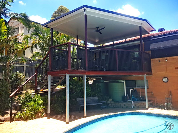 A back deck over a pool by SEQ Builders